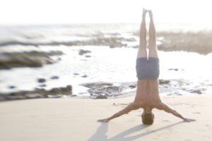 Man Practicing Yoga On The Beach Rheuma Akademie