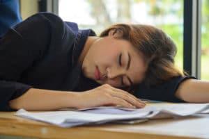 Frau schlafend am Tisch Rheuma Akademie